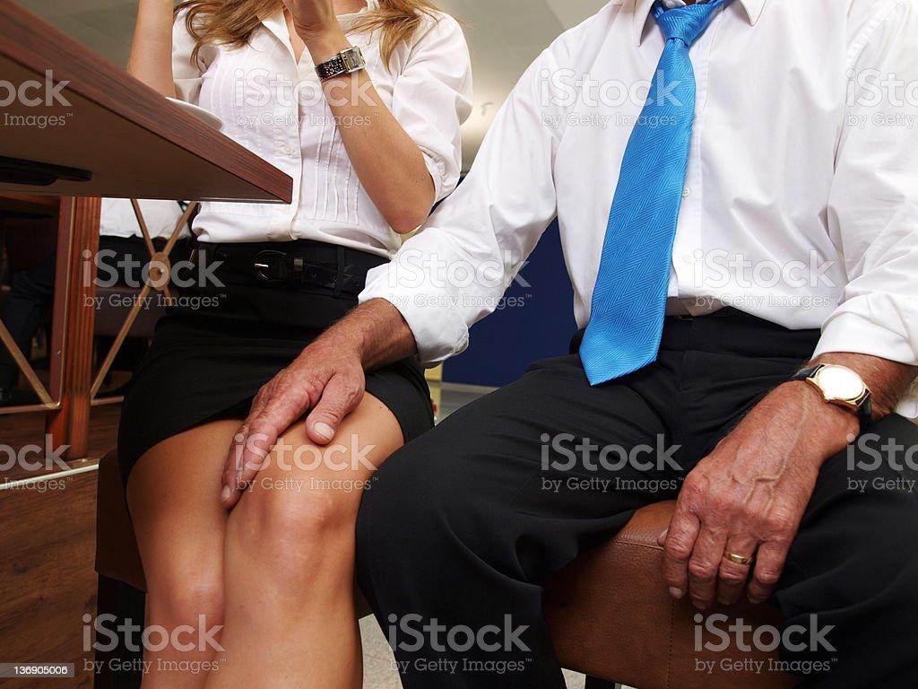 Man's hand on woman's knee stock photo