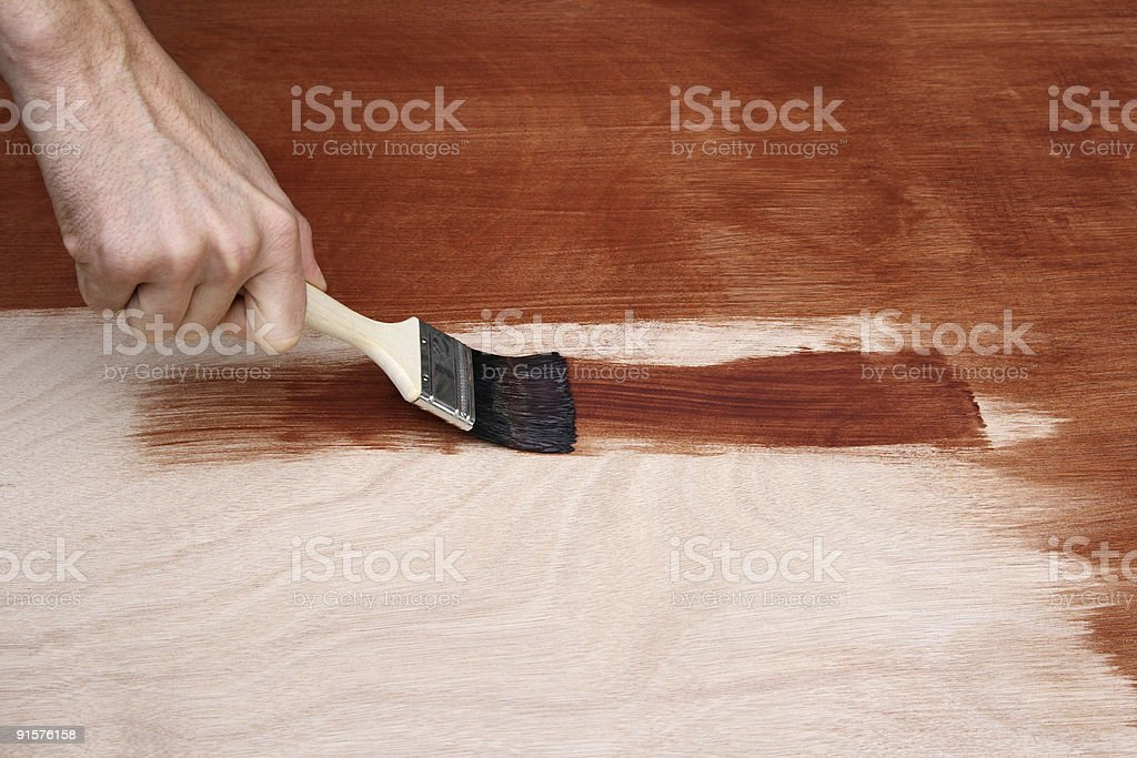 Man's hand painting a wooden surface royalty-free stock photo