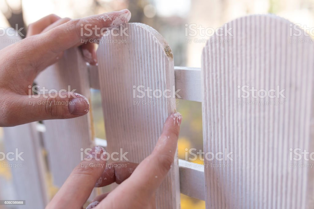 Man's hand painting wooden fence stock photo