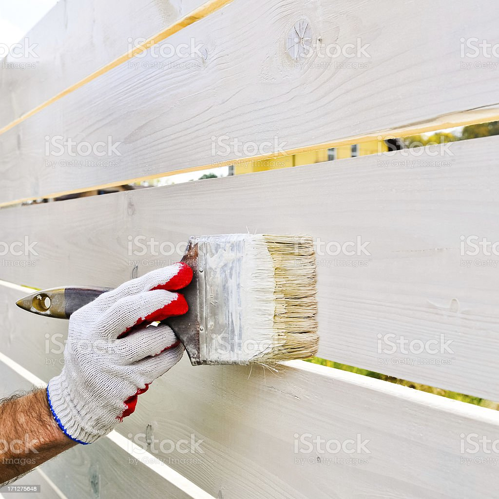 Man's hand painting wooden fence with brush on white colour stock photo