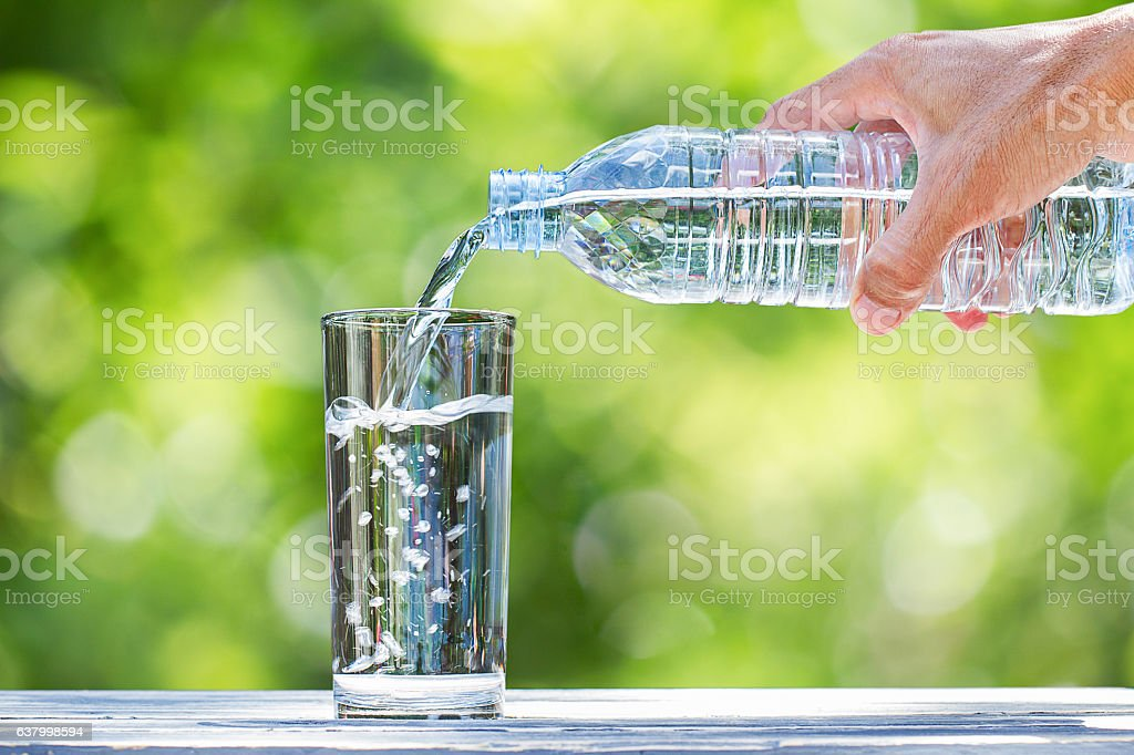 Man's hand pouring water into glass on blurred bokeh background stock photo