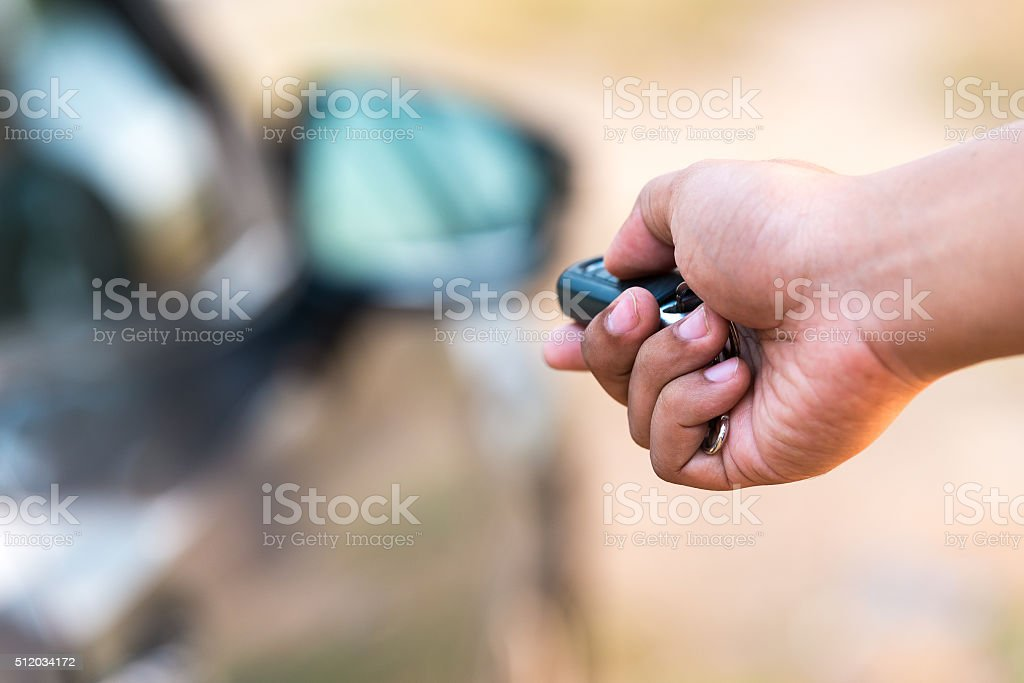 Man's hand pushing unlock button on car remote stock photo