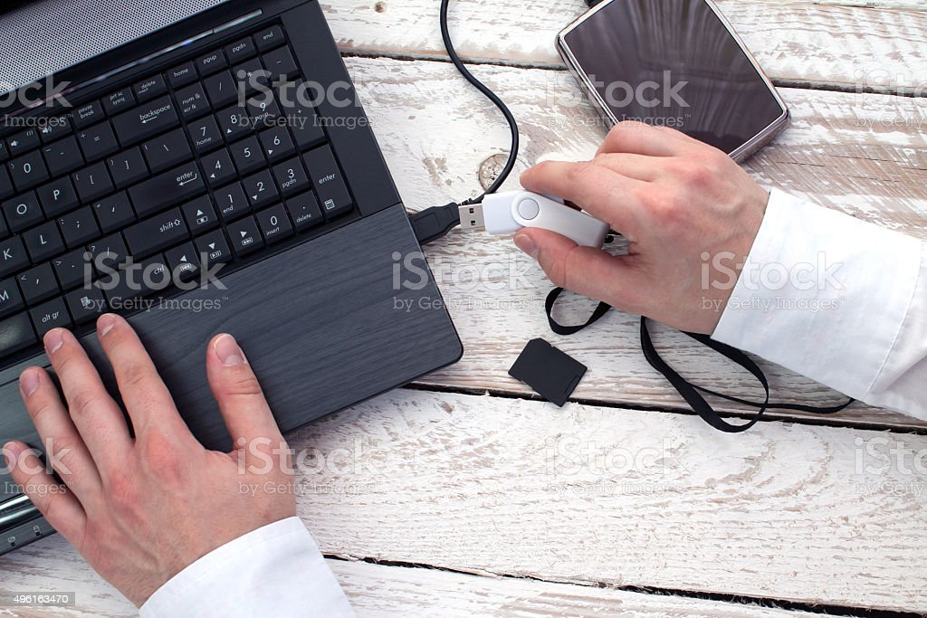 Man's hand puts pendrive into laptop. stock photo