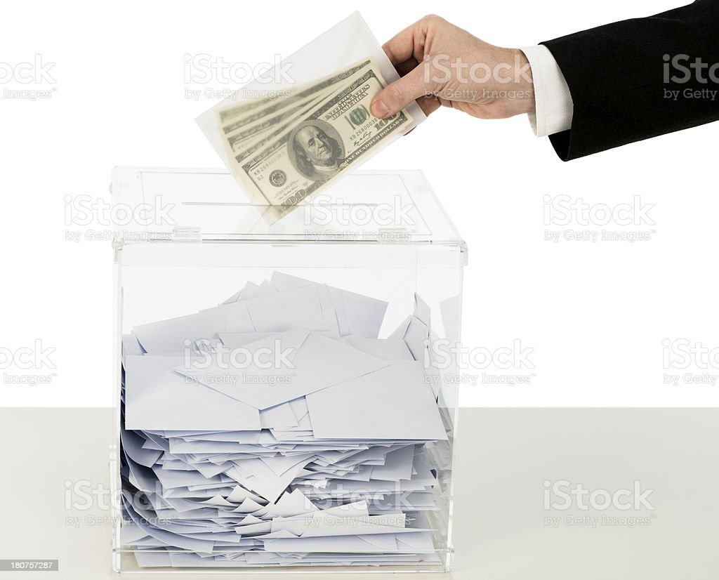 A mans hand putting money in to a ballot box stock photo