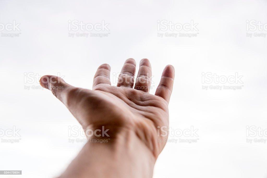 man's hand reaching towards the sky stock photo