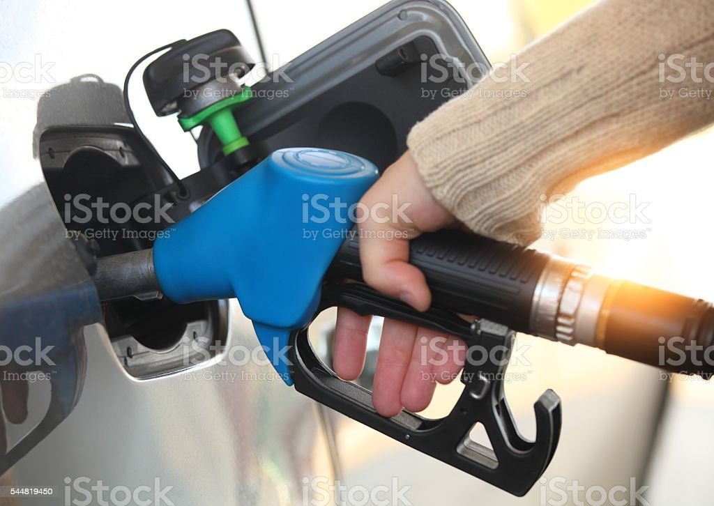 Mans hand refilling the car with a gas pump stock photo