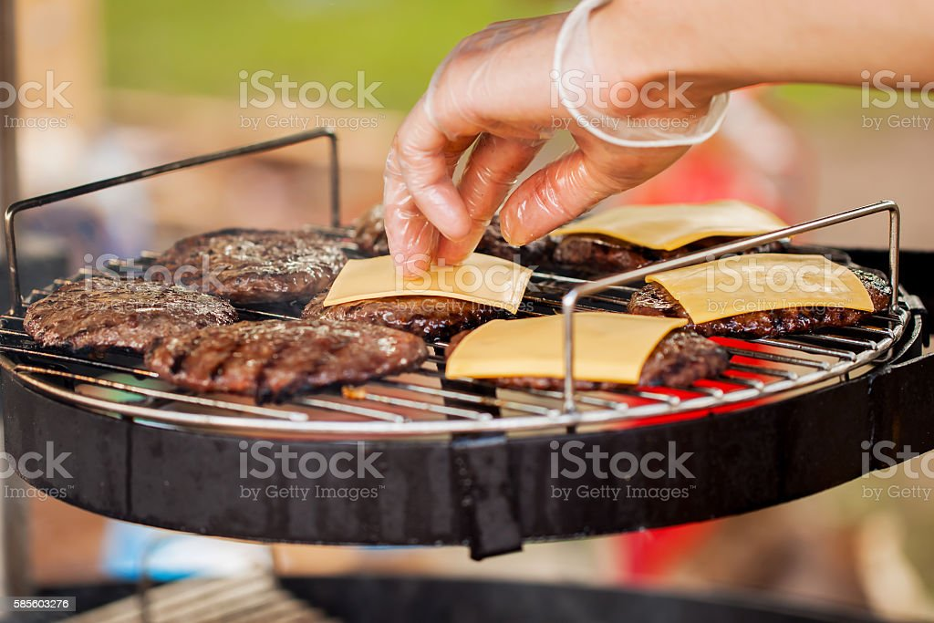 Man's hand, spread the cheese on the burgers stock photo