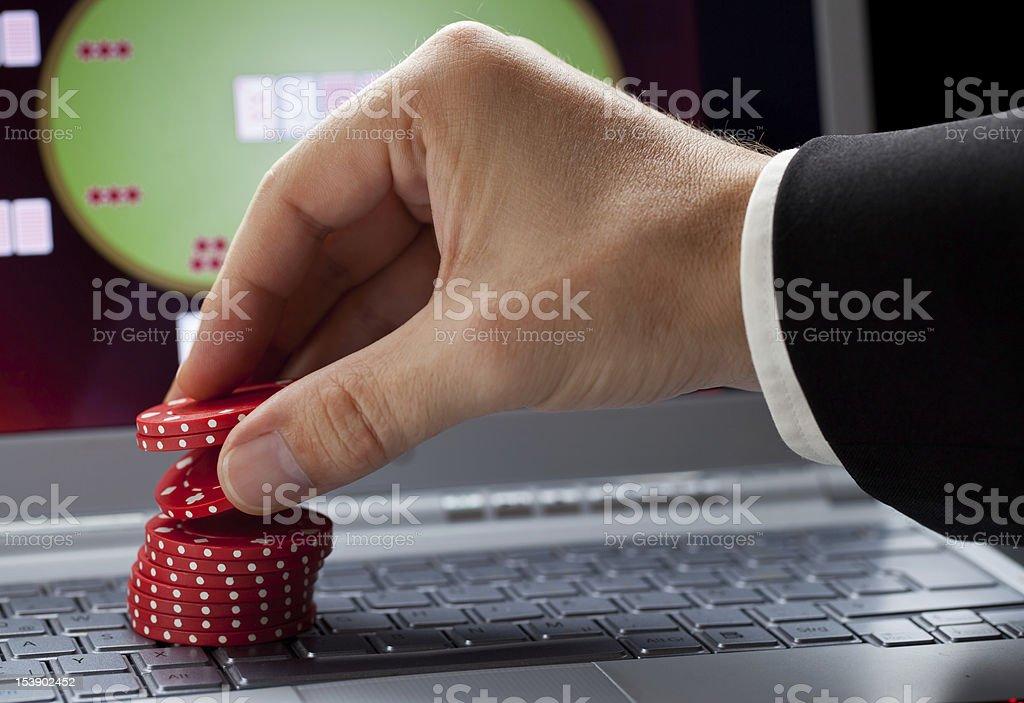 Man's hand stacking casino chips on laptop keyboard royalty-free stock photo