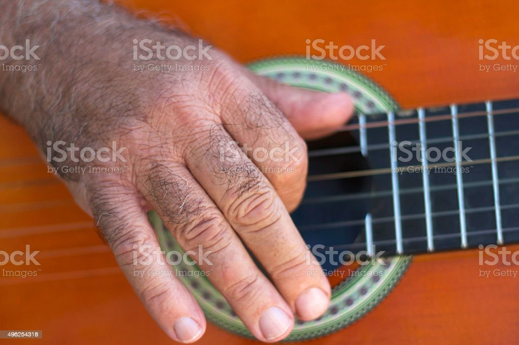 Man's Hand Strumming Classical Guitar (Close-Up) stock photo