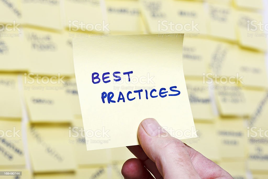Man's hand takes 'Best Practices' note from business buzzword noticeboard stock photo