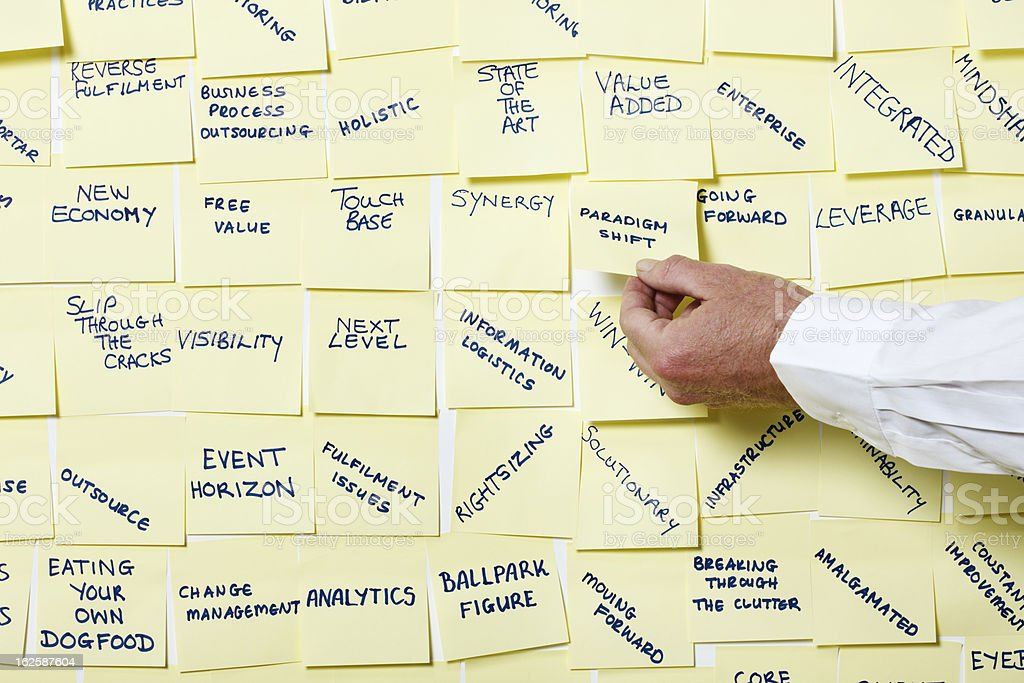 Man's hand takes 'Paradigm Shift' note from noticeboard of buzzwords royalty-free stock photo
