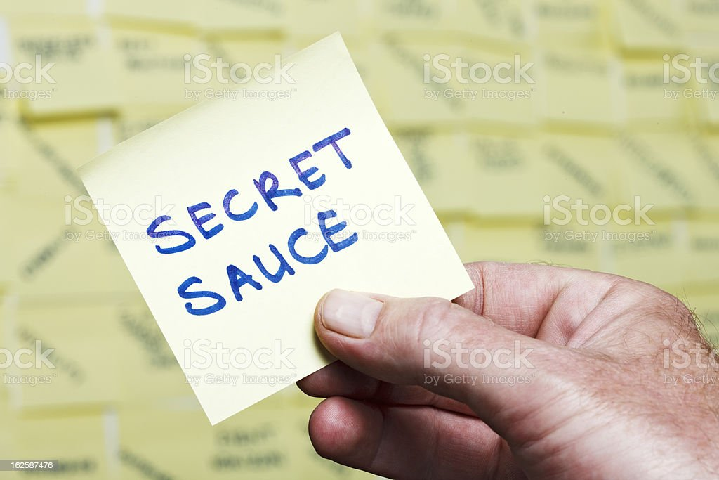 Man's hand takes 'Secret Sauce' note from noticeboard of buzzwords stock photo