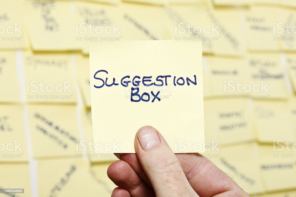 Man's hand taking note 'Suggestion Box' from wall of buzzwords stock photo