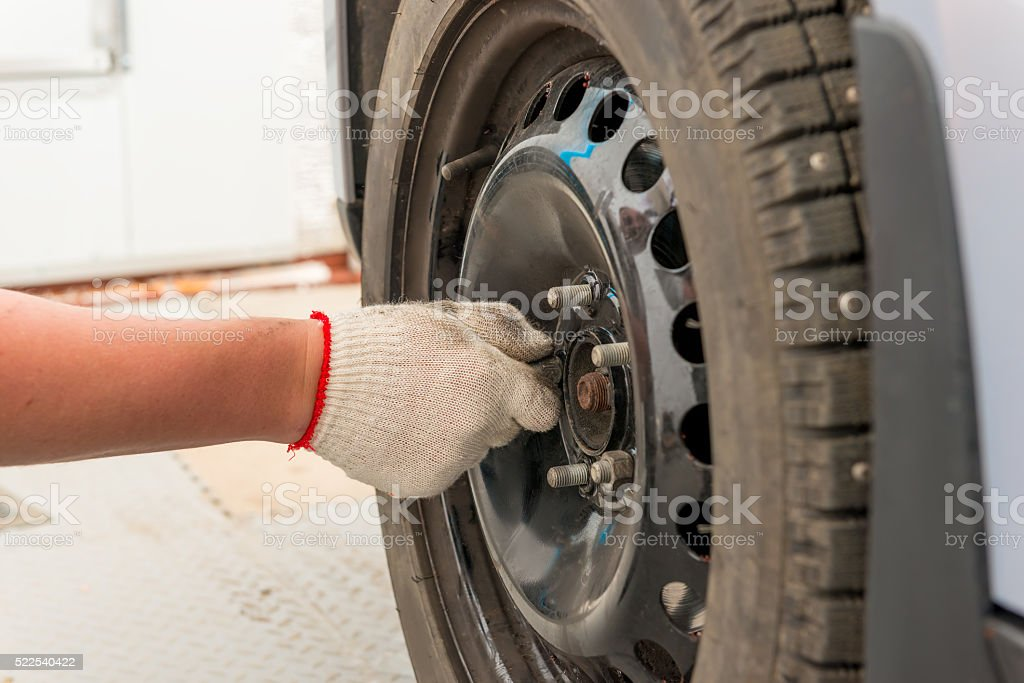 man's hand tightening the screws on the wheel after installation stock photo
