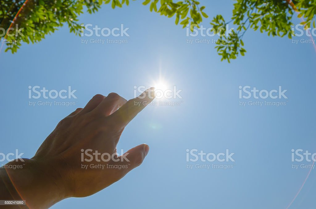 Man's Hand Touching The Sun stock photo
