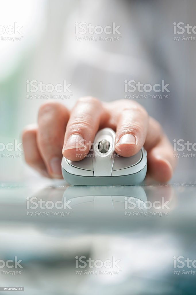 Man's hand using cordless mouse on glass table. stock photo