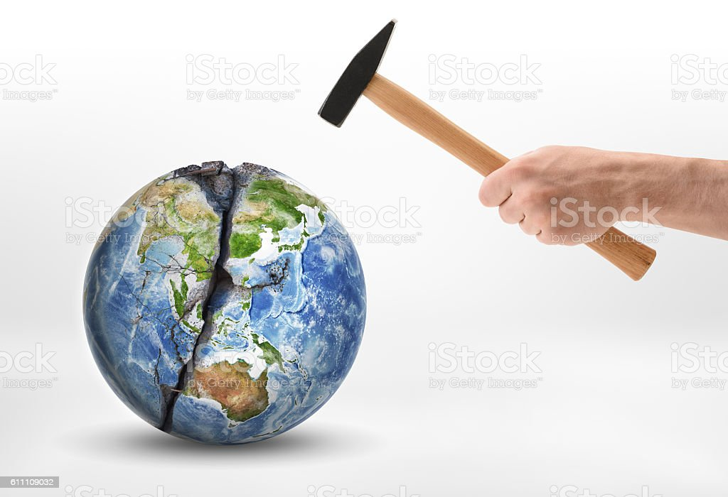 Man's hand with a hammer hits the planet Earth. stock photo