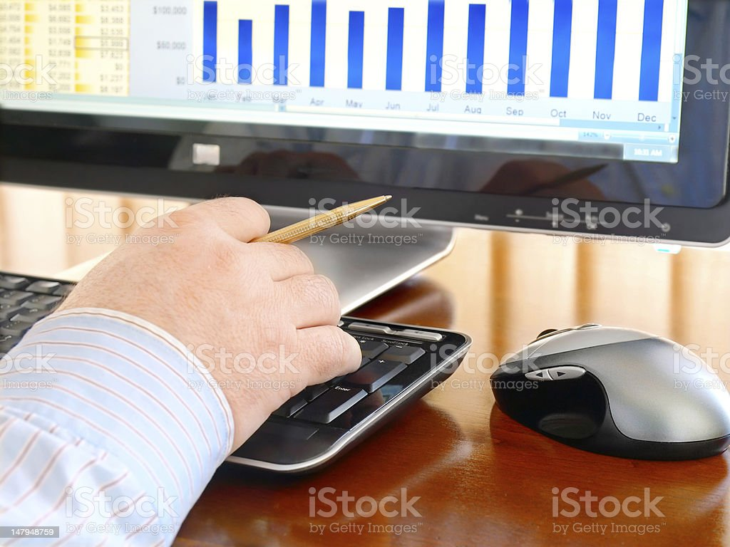 Man's Hand with Pen Typing at a Computer Keyboard royalty-free stock photo