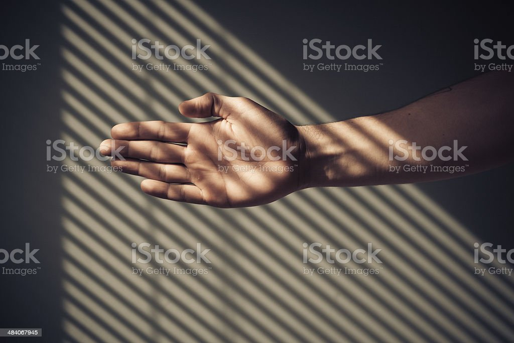 Man's hand with shadows from blinds stock photo