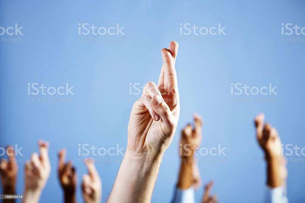 Man's hand with superstitiously crossed fingers, more in blue background stock photo