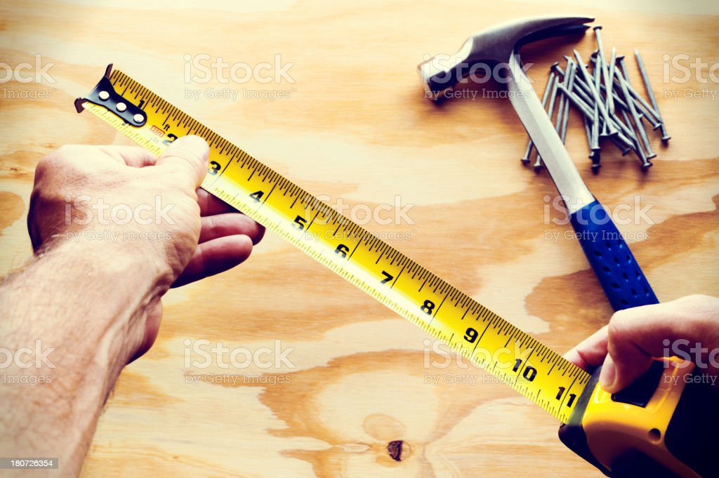 Man's Hand with Tape Measure Nails and Hammer on Wood royalty-free stock photo