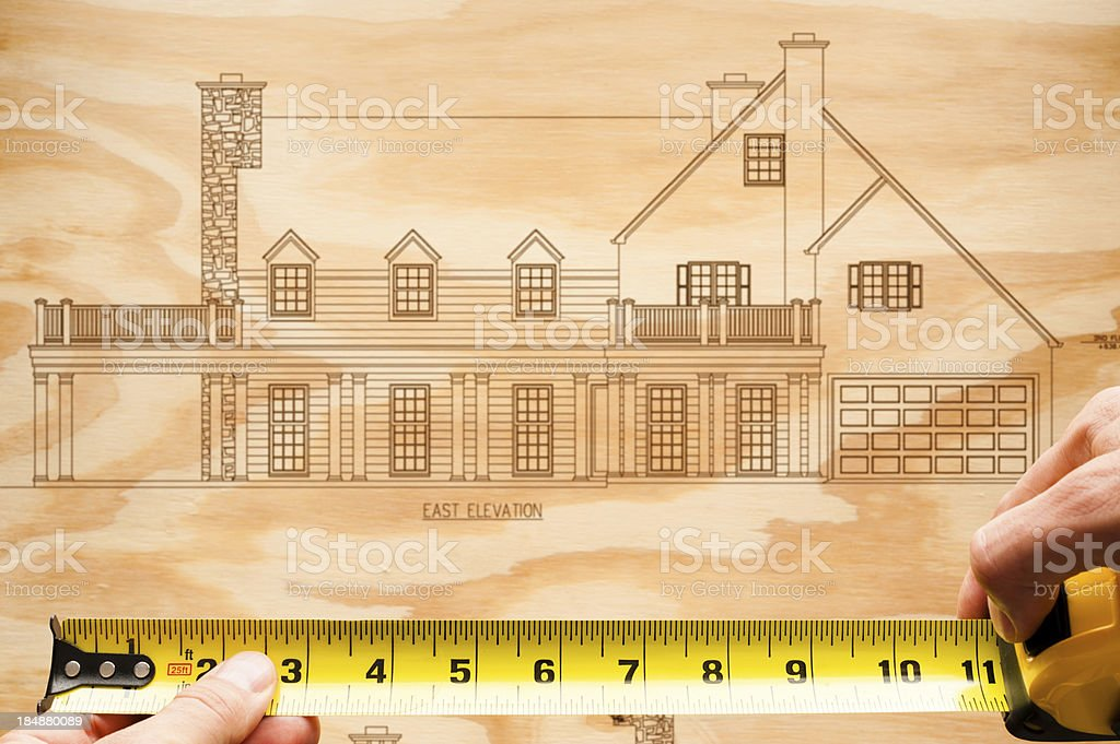 Man's Hand with Tape Measure on Wood House Elevation royalty-free stock photo