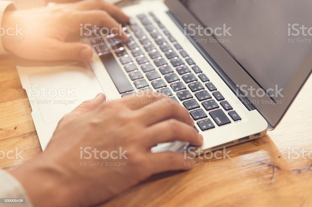 man's hand working with laptop computer notebook, selective focu stock photo