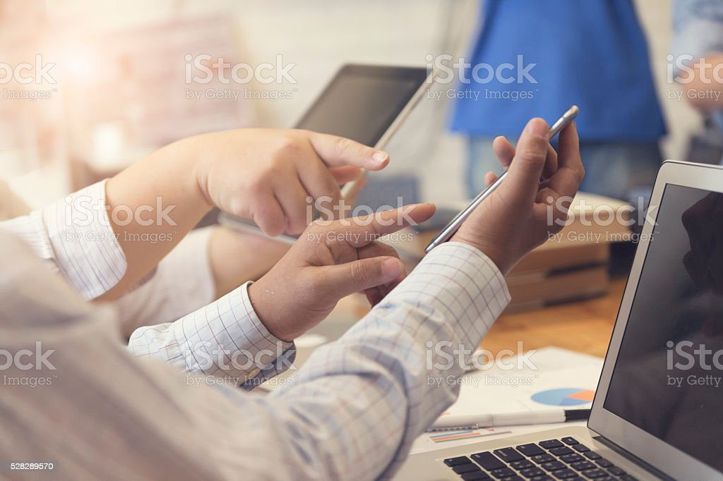 man's hand working with mobile phone, tablet, document and lapto stock photo
