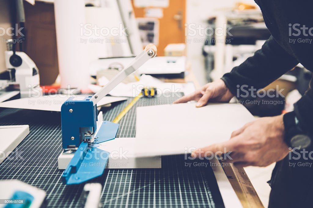 Man's Hands Adjusting Material for Manual Hole Punch Machine stock photo