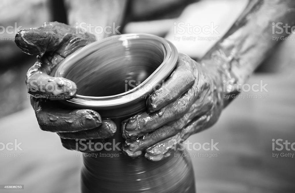 Man's hands creating pottery on wheel stock photo