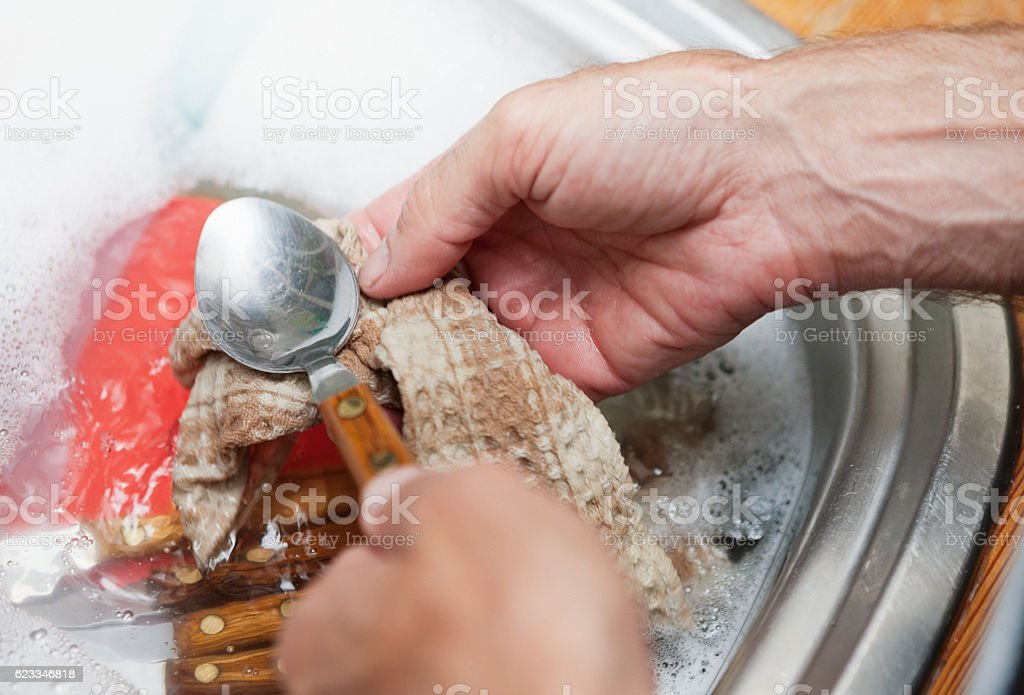 Man's hands doing the dishes, seen from above stock photo