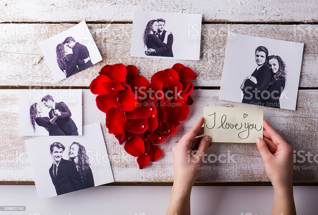 Mans hands. His and his girlfriends photo. Rose petal heart. stock photo