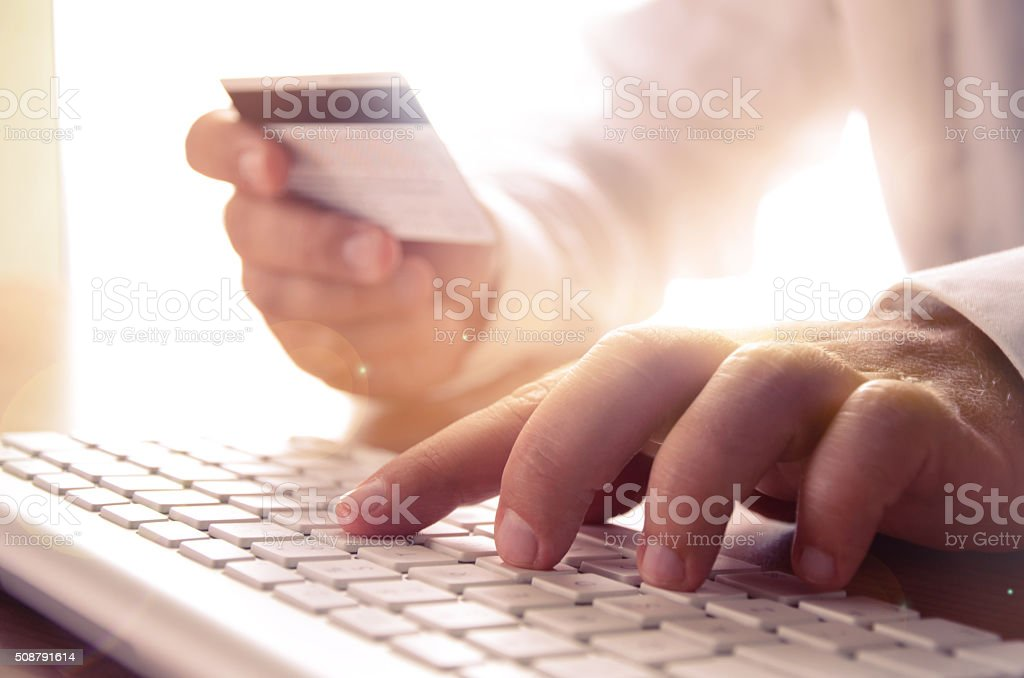 Man's hands holding credit card and using computer keyboard stock photo