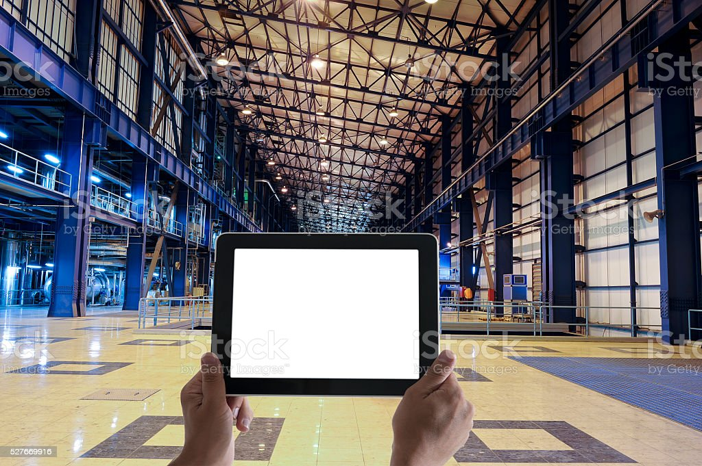 Man's hands holding digital tablet computer in Industrial Building stock photo