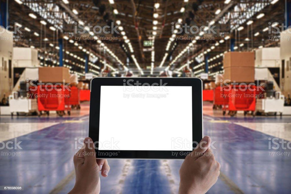 Man\'s hands holding digital tablet computer in Industrial Building