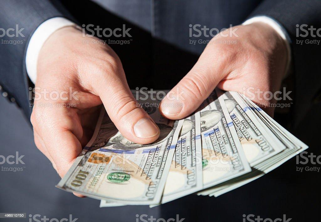 Man's hands holding dollars stock photo