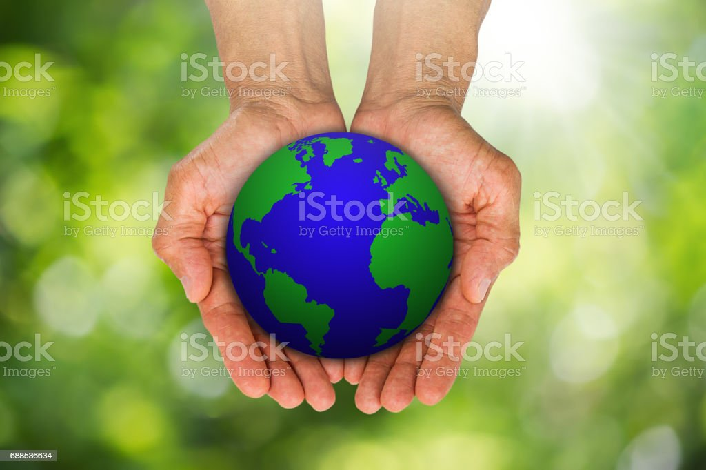 Man's hands holding globe on blurred green bokeh background, environment concept stock photo