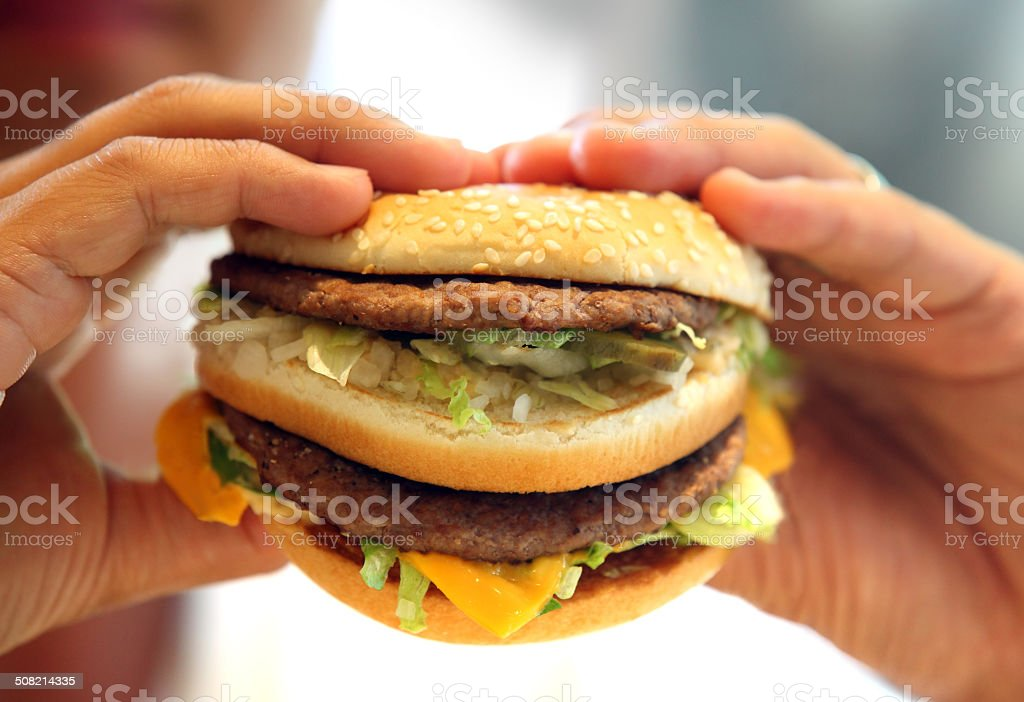 man's hands, holding onto a burger stock photo