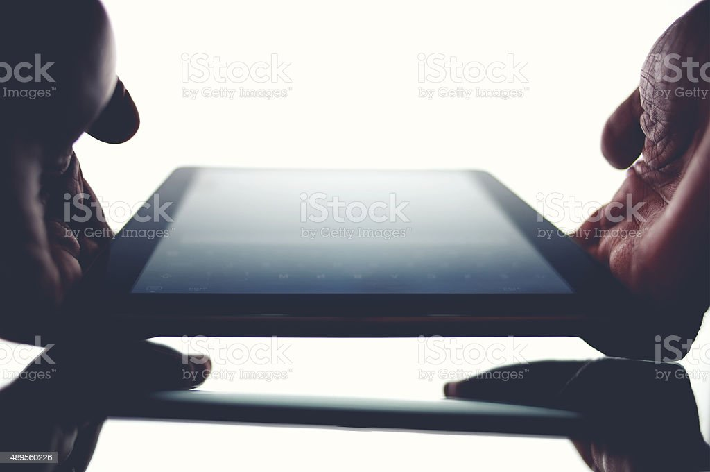 Man's hands holding touchpad with beautiful screen reflection stock photo