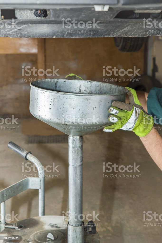 Man's hands in protective gloves changing oil filter. stock photo