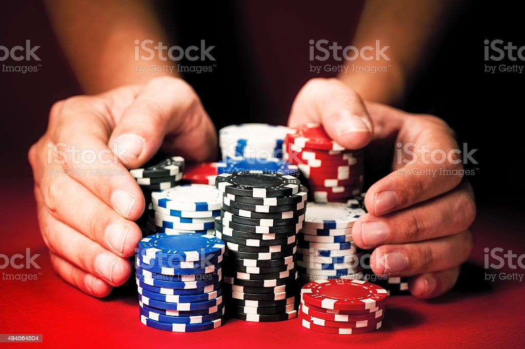 Man's hands move the winnings casino chips on red table. stock photo