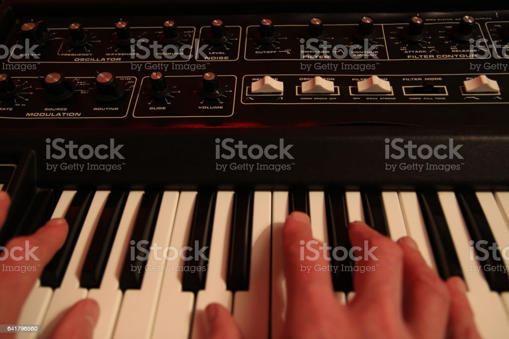 Man's hands playing a vintage retro analogue synth stock photo