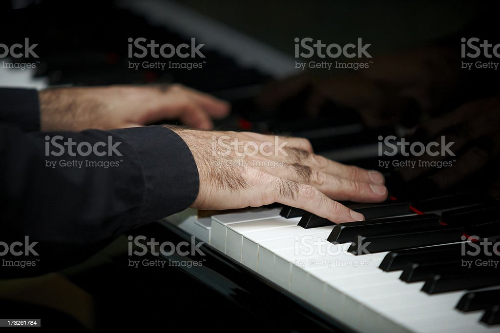 Man's hands playing piano stock photo