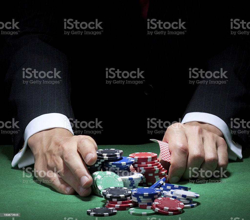 Man's hands pushing poker chips and holding cards on a table stock photo