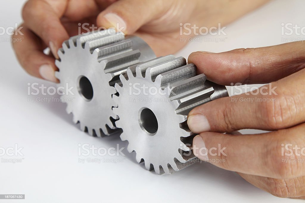 Man's hands put together two steel gears royalty-free stock photo