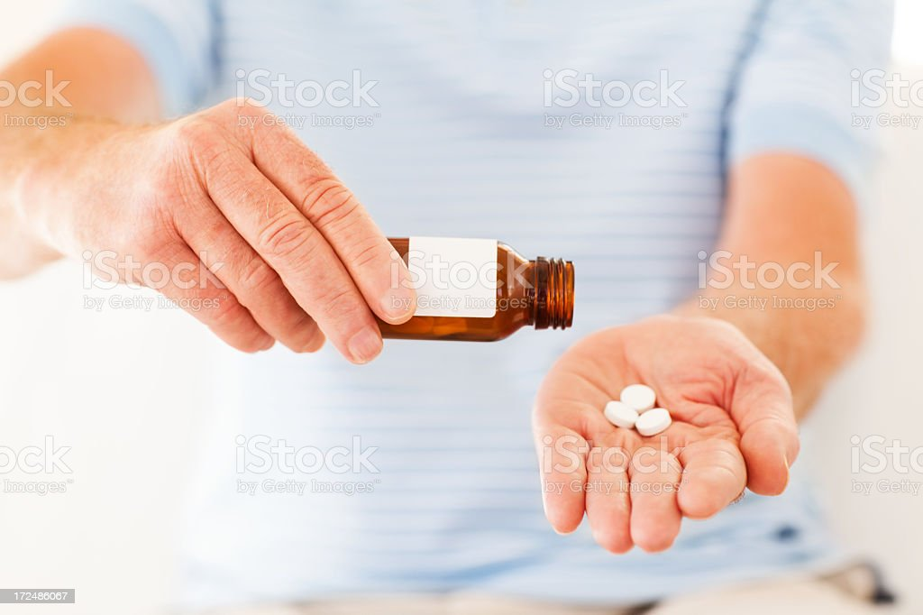 Man's Hands Removing Pills From Bottle royalty-free stock photo