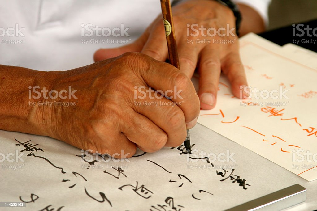 Man's hands shown drawing Japanese calligraphy stock photo