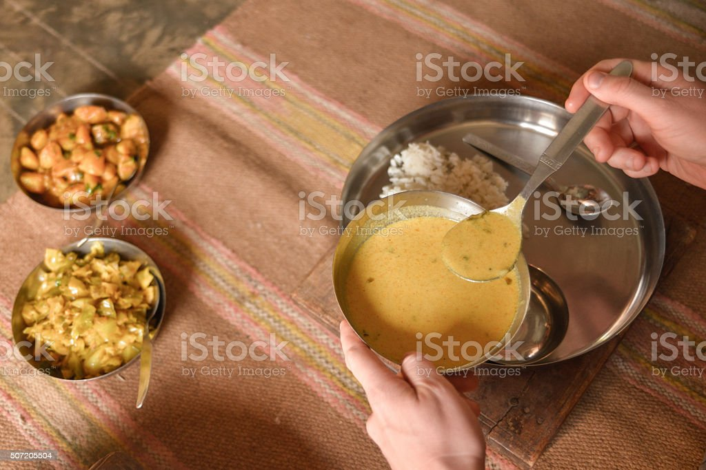 Man's Hands Spooning Lentil Soup Amongst Other Dishes, India stock photo