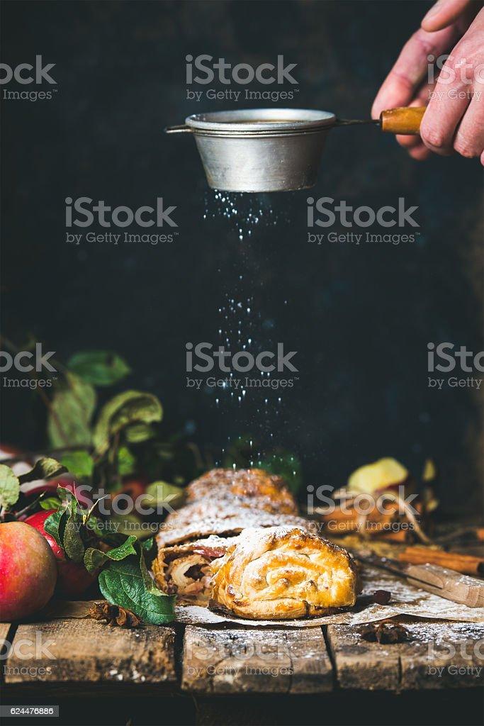 Man's hands sprinkling sugar powder on apple strudel cake stock photo