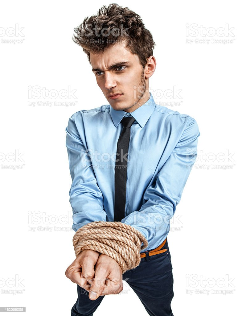 Man's hands tied together with rope stock photo